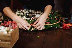 Desenhista de sorriso bonito novo da mulher que prepara a grinalda sempre-verde da árvore do Natal Fabricante da decoração do Nat imagens de stock