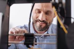 Desenhista deleitado feliz que trabalha com uma impressora 3d Fotos de Stock