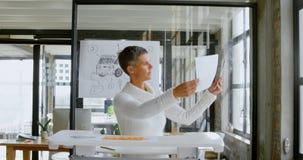 Desenhista do carro que verifica o projeto do esboço do carro no escritório 4k vídeos de arquivo
