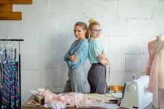 Desenhista dois fêmea consideravelmente novo que olha a câmera em costurar a oficina imagens de stock