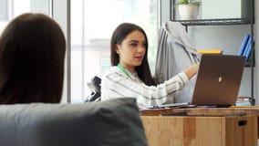 Desenhista fêmea atrativo novo que discute o t-shirt com seu colega video estoque