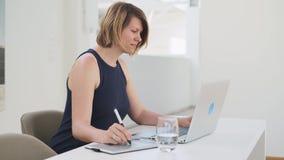 Desenhista fêmea branco novo que trabalha em um portátil usando uma tabuleta gráfica da pena vídeos de arquivo