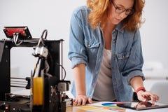 Desenhista fêmea inteligente que inclina-se sobre a tabela Imagens de Stock