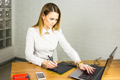 Desenhista fêmea no escritório que trabalha com a tabuleta gráfica e o portátil digitais Retoucher da fotografia que senta-se na  fotografia de stock royalty free