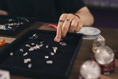 Desenhista fêmea que faz joias em uma loja de joia Fotos de Stock