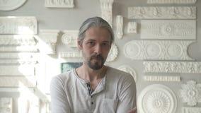 Desenhista masculino com o cabelo cinzento que está em seu estúdio brilhante vídeos de arquivo