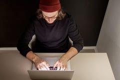 Desenhista ou programador no local de trabalho homem novo em um chap?u e nos vidros que sentam-se em um port?til fotografia de stock