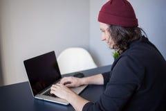 Desenhista para um portátil, um local de trabalho para freelancers Um homem novo que senta-se em uma tabela fotografia de stock