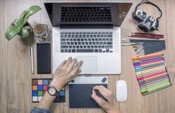 Desenhista que usa o laptop e a tabuleta de gráficos em casa offic fotos de stock royalty free