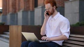 Desenhista Talking no telefone ao sentar-se no banco, discutindo video estoque