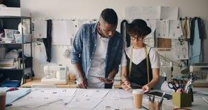 Desenhistas de roupa do homem e da mulher que usam esboços de tiragem da tabuleta no estúdio filme