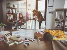 Desenhistas focalizados que criam a roupa nova foto de stock