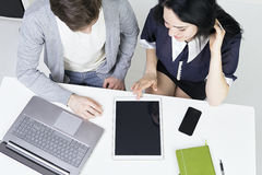 Desenhistas ocasionais de sorriso da vista superior que trabalham com portátil e tabuleta no escritório Trabalhos de equipa do wo Imagens de Stock Royalty Free