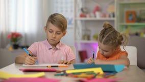 Desenho adorável do menino e da menina pelos lápis que sentam-se na tabela, lazer do jardim de infância video estoque