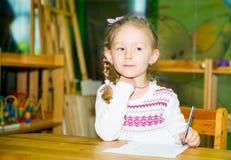 Desenho adorável da menina da criança com os lápis coloridos na sala do berçário Criança no jardim de infância na classe do pré-e Imagens de Stock