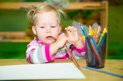 Desenho adorável da menina da criança com os lápis coloridos na sala do berçário Criança no jardim de infância na classe do pré-e Fotos de Stock Royalty Free