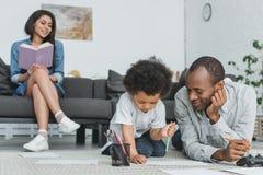 desenho afro-americano do pai com o livro de leitura do filho e da mãe foto de stock royalty free