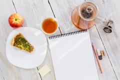 Desenho-almofada, copo do chá, torta da galinha, bule do maçã, o de vidro e relógio na tabela de madeira Fotografia de Stock Royalty Free
