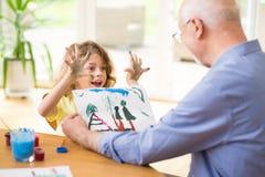 Desenho bonito da exibição da criança a seu avô fotografia de stock