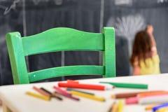 Desenho bonito e pintura da menina no jardim de infância Clube criativo das crianças das atividades imagem de stock