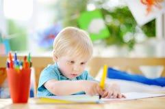 Desenho bonito e pintura do rapaz pequeno com as penas de marcadores coloridas no jardim de infância foto de stock
