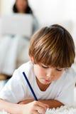 Desenho concentrado do rapaz pequeno que encontra-se no assoalho Imagens de Stock Royalty Free