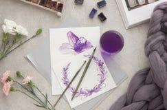 Desenho da aguarela Escova do espaço de trabalho do artista, pena, aquarela, ramalhete de rosas cor-de-rosa em um fundo de pedra  fotografia de stock