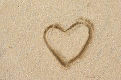 Desenho da forma do coração em uma praia da areia Fotografia de Stock