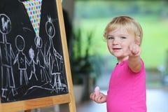 Desenho da menina da criança em idade pré-escolar na placa preta Fotografia de Stock Royalty Free