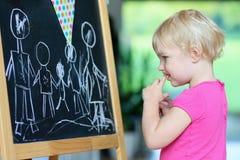 Desenho da menina da criança em idade pré-escolar na placa preta Fotos de Stock Royalty Free