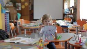 Desenho da menina na tabela na sala de aula Educação Criança que senta-se em uma mesa vídeos de arquivo
