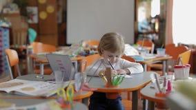 Desenho da menina na tabela na sala de aula Educação Criança que senta-se em uma mesa filme
