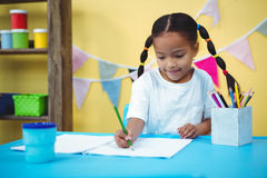 Desenho de sorriso da menina em seu livro de coloração imagem de stock