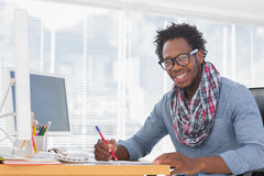 Desenho de sorriso do desenhista com um lápis vermelho em uma mesa Fotografia de Stock