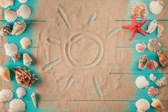 Desenho de Sun na areia entre conchas do mar Fotos de Stock