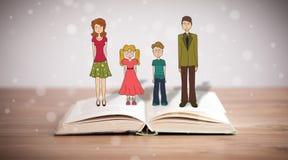 Desenho de uma família feliz no livro aberto Fotos de Stock Royalty Free