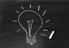 Desenho de uma ideia do bulbo na placa preta Fotos de Stock Royalty Free