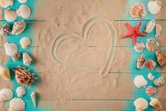 Desenho do coração na areia entre conchas do mar Fotografia de Stock Royalty Free