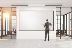 Desenho do homem de negócios em um whiteboard no escritório Imagem de Stock