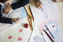 Desenho do menino com os pastéis na tabela Fotografia de Stock Royalty Free