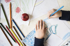 Desenho do menino com os pastéis na tabela Fotos de Stock