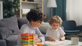 Desenho do rapaz pequeno com a mamã de inquietação na tabela na sala clara no apartamento de estúdio