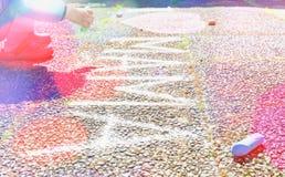 Desenho do rapaz pequeno do cora??o cor-de-rosa com giz no passeio imagem de stock