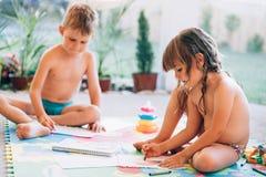 Desenho do rapaz pequeno e da menina com pastéis fotos de stock royalty free
