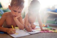 Desenho do rapaz pequeno e da menina com pastéis foto de stock