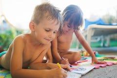 Desenho do rapaz pequeno e da menina com pastéis imagem de stock