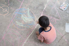 Desenho e coloração do rapaz pequeno pelo giz na atividade à terra da arte Foto de Stock