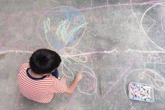 Desenho e coloração do rapaz pequeno pelo giz na atividade à terra da arte Imagens de Stock