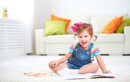 Desenho feliz da menina da criança com os lápis coloridos que encontram-se no assoalho Imagens de Stock Royalty Free