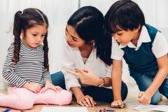 Desenho feliz da pintura do jardim de infância da menina da criança da criança da família no peper imagens de stock